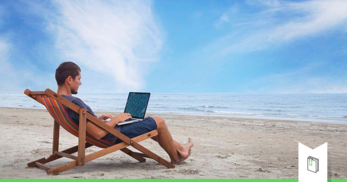 man ligstoel laptop strand zomer